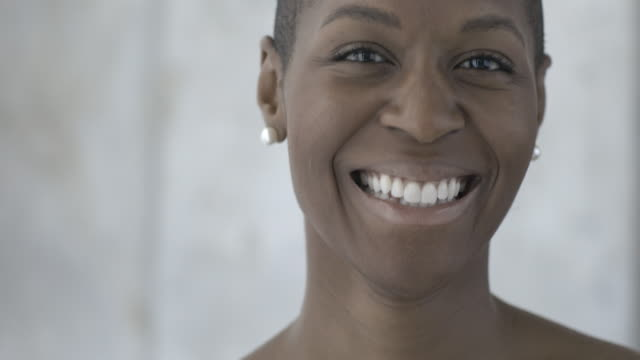 Young African American woman with shaved head gently smiles and laughs into camara