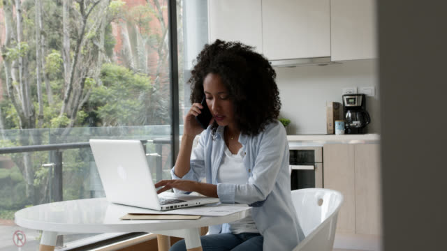 young african american woman working from home and talking on the phone while typing on computer - mobile phone stock videos & royalty-free footage