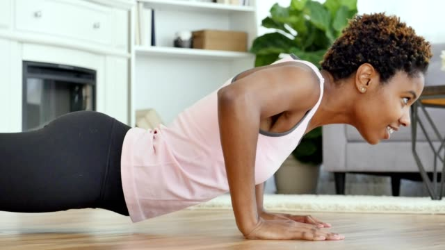 young african american woman working out at home - prendersi cura del corpo video stock e b–roll