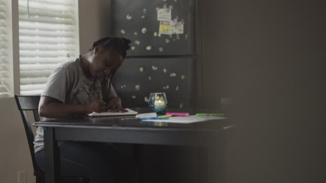 SLO MO. Young African American woman writes in notebook on kitchen table.