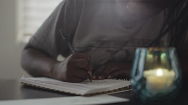 cu slo mo. young african american woman writes in notebook. - studying stock videos & royalty-free footage