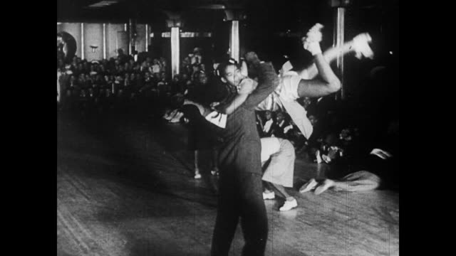 / young african americans swing dancing on the dance floor / partners dance with numbered backs in competition / cu band african american swing dance... - 1940 bildbanksvideor och videomaterial från bakom kulisserna