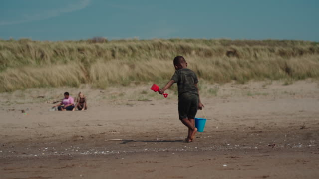 young african boy carrying a bucket of sand