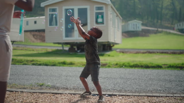young african boy catches bubbles