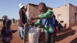 Young african boy collecting water from a tap while woman line up to collect water in plastic containers due to severe drought in South Africa