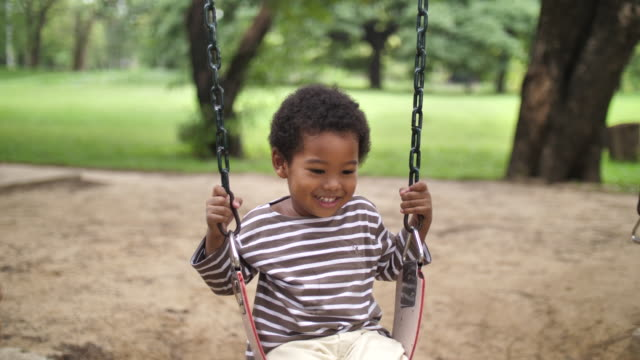 young african  boy on swing in outdoor playground - swinging stock videos & royalty-free footage