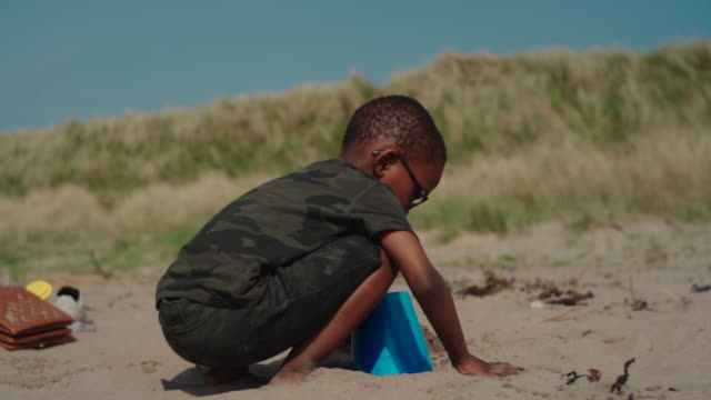 young african boy playing with sand