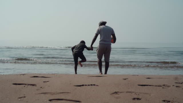 young african boy running away from the cold sea water