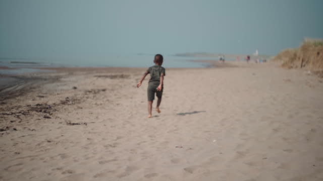 young african boy running away on the beach
