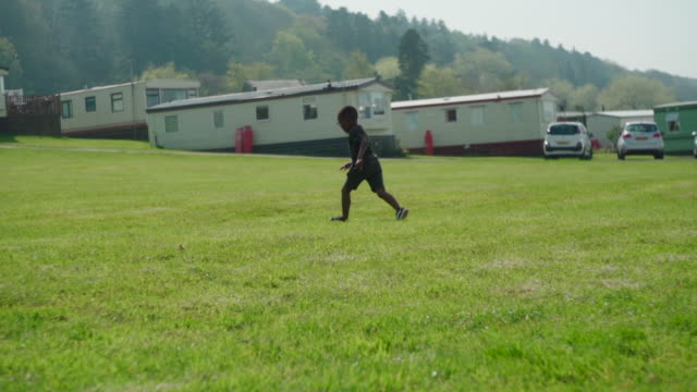 young african boy running to pick up beach ball