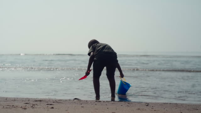 young african boy shaking off sand in the water