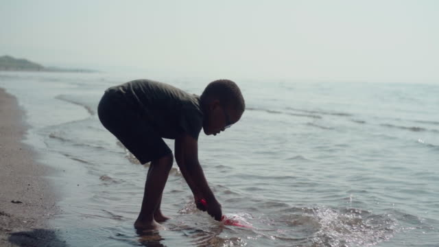 young african boy splashing sea water