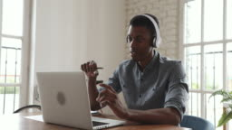 Young african businessman wear headphone video calling on laptop