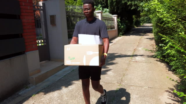 young african delivery man delivering package with groceries - part time worker stock videos & royalty-free footage