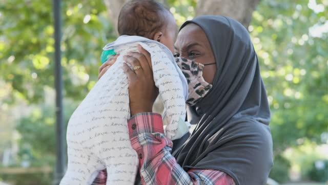 vidéos et rushes de jeune femme d'ascendance africaine posant avec son bébé utilisant un masque protecteur de visage - 2 5 mois