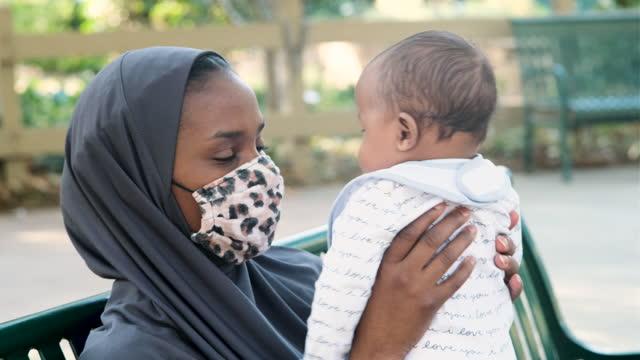 保護フェイスマスクを着用して彼女の赤ちゃんとポーズをとる若いアフリカ系の女性 - アフリカ系カリブ人点の映像素材/bロール