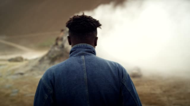young african ethinicity man in surreal landscape. hissing steam vents - geyser stock videos and b-roll footage