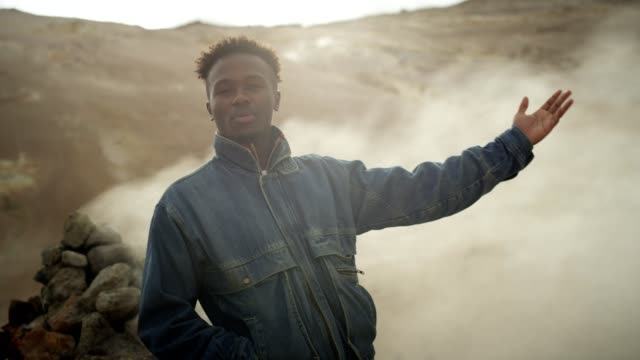 young african ethnicity man in surreal landscape. hissing steam vents - reaching stock videos and b-roll footage