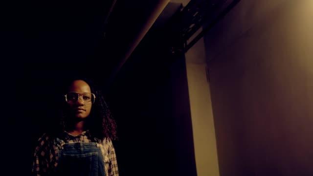 vídeos y material grabado en eventos de stock de trabajadora de origen étnico africano joven en corredor sombrío - inmigrante