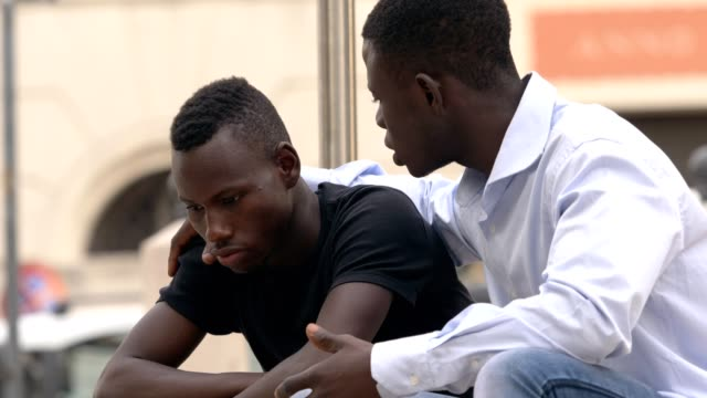 Young African man embracing his sad friend
