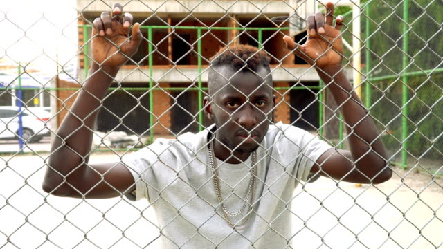 young african man in the ghetto - wire mesh fence stock videos & royalty-free footage