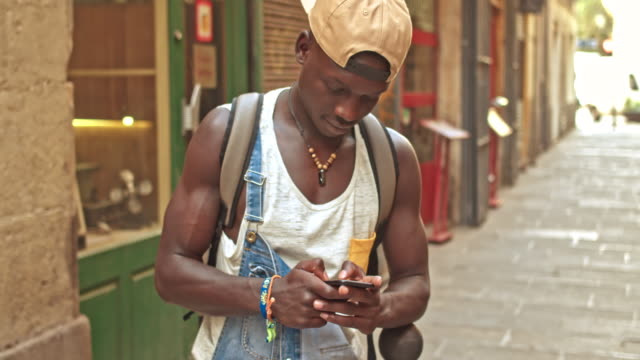 young african man sending a text message on the mobile phone in the street - baseball cap stock videos & royalty-free footage