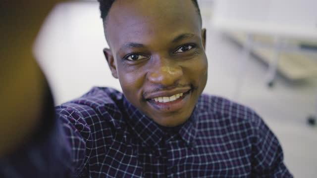 vídeos de stock, filmes e b-roll de jovem africano usando celular para chamada de vídeo. - só um homem