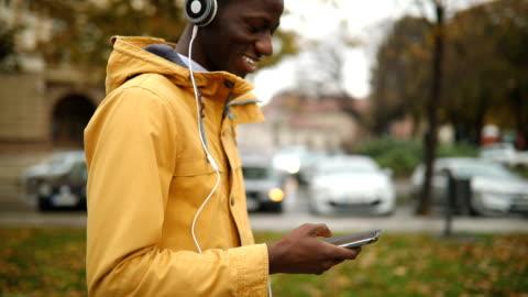 vidéos et rushes de jeune homme africain à l'aide de téléphone - casque