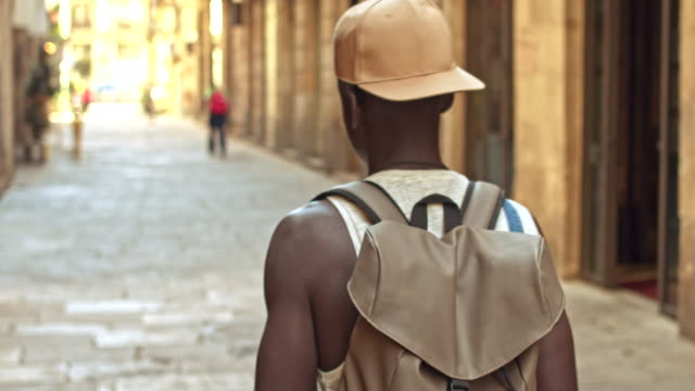 young african man walking in the city - zaino da montagna video stock e b–roll