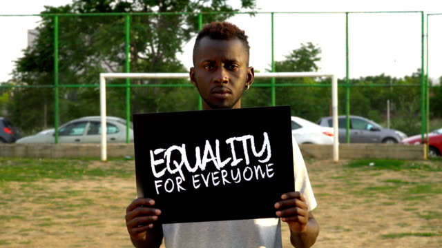 young african protestor is holding cardboard ''equality for everyone'' - racism stock videos & royalty-free footage
