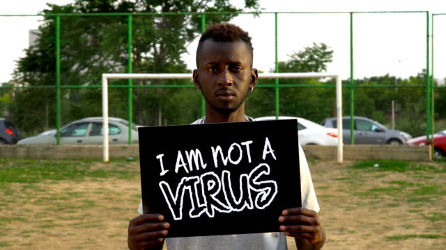 Jonge Afrikaanse Demonstrant houdt karton ''I AM NOT VIRUS''