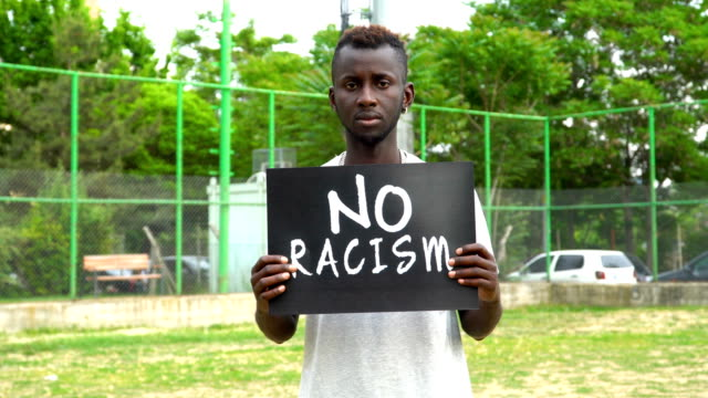 young african protestor is holding cardboard ''no racism'' - anti racism stock videos & royalty-free footage