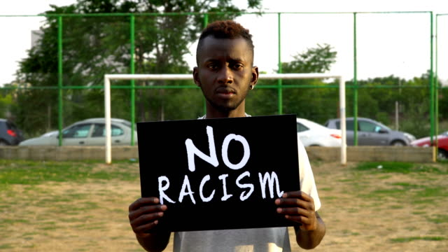 young african protestor is holding cardboard ''no racism'' - rebellion stock videos & royalty-free footage