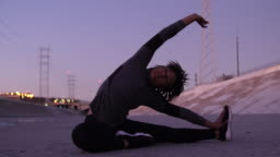Young african woman doing stretching workout