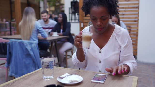 young african woman siting at outdoor cafe and checking social media - mid adult stock videos & royalty-free footage