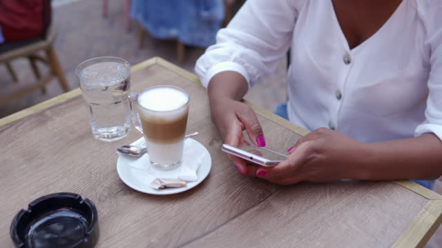 young african woman siting at outdoor cafe and text messaging - human hand stock videos & royalty-free footage