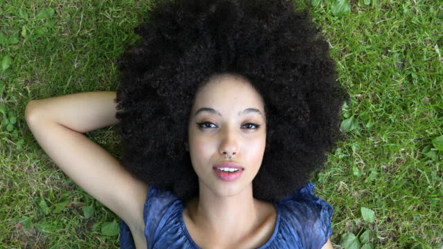 young african woman with arms open enjoying fresh air in summertime - sdraiato video stock e b–roll