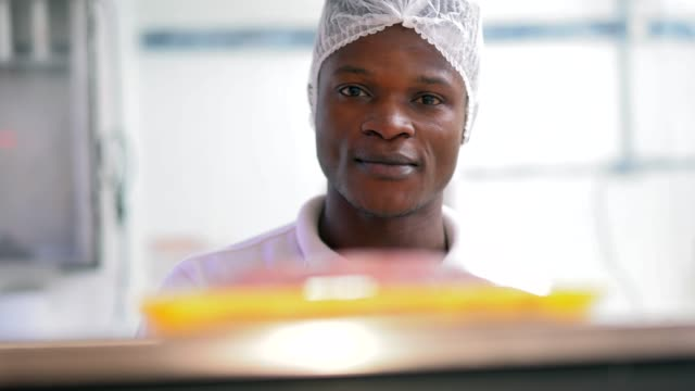Young african working at the butchery weighing the meat
