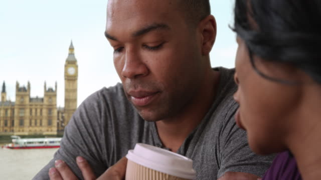 Young African-American boyfriend reluctantly listens to girlfriend near Big Ben