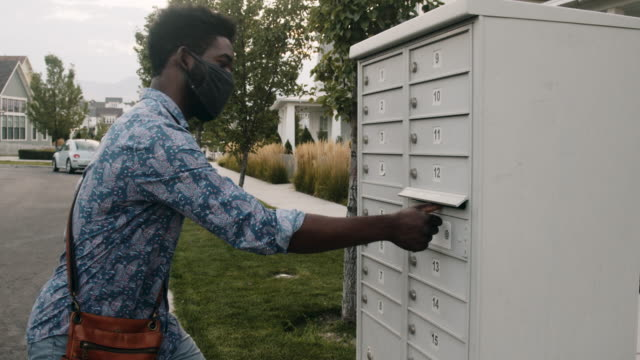 young african-american couple in their twenties walking to a mail box to mail in their ballot for voting - voting ballot stock videos & royalty-free footage