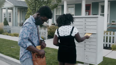 vidéos et rushes de jeunes couples afro-américains dans la vingtaine marchant à une boîte aux lettres pour envoyer dans leur bulletin de vote pour voter - bulletin de vote