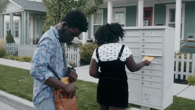 young african-american couple in their twenties walking to a mail box to mail in their ballot for voting - letterbox stock videos & royalty-free footage