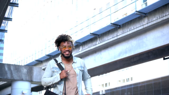 young african-american man in the city, walking - denim jacket stock videos & royalty-free footage