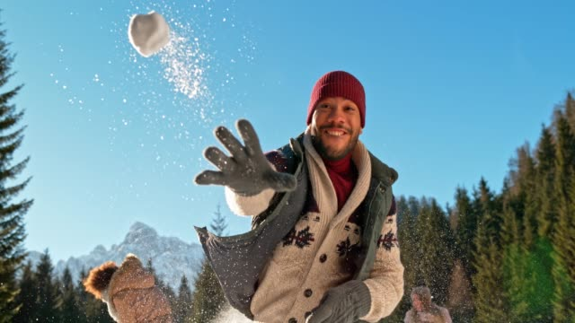 slo mo young african-american man throwing a snowball into the camera - lanciare video stock e b–roll