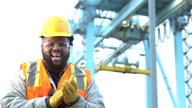 Young African-American man working at seaport, laughing