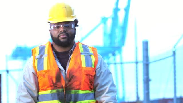 vídeos de stock, filmes e b-roll de homem jovem afro-americano, trabalhando no porto de transporte - porto comercial