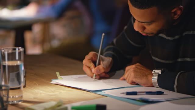 vídeos y material grabado en eventos de stock de hombre afroamericano joven trabajando hasta tarde en el inicio de oficina - lapiz