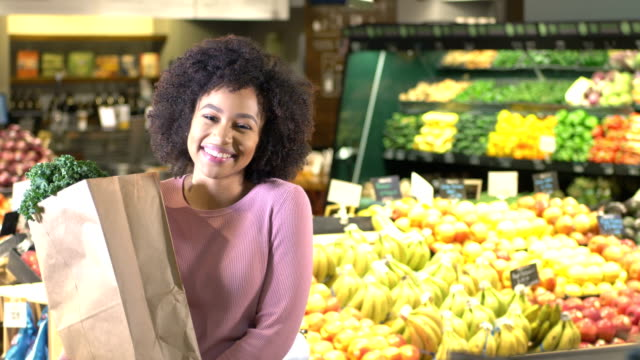 young african-american woman buying groceries - paper bag stock videos & royalty-free footage