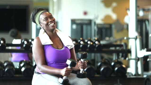 Young African-American woman in gym holding dumbbells