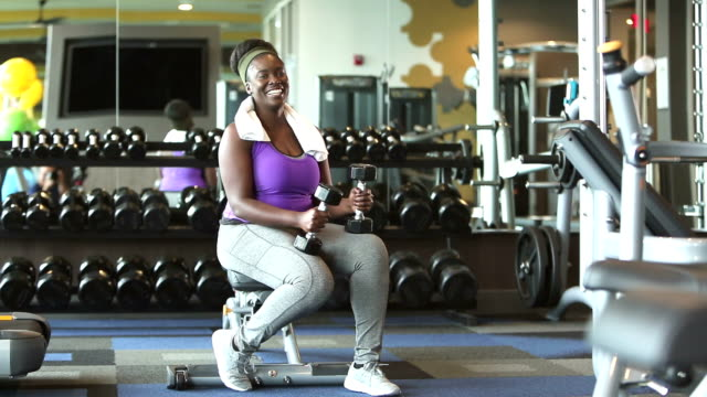 young african-american woman in gym holding dumbbells - hand weight stock videos & royalty-free footage